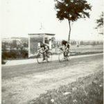 Derriére les cyclistes on devine l'ancien poids public